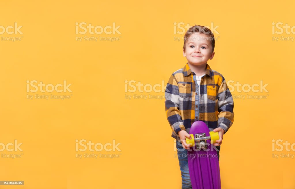smiling little boy standing with skateboard stock photo