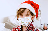 istock Smiling Little boy wearing a Santa hat and a protective face mask looking at the camera 1278696426