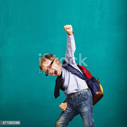 istock smiling little boy with big backpack jumping and having fun 577350268