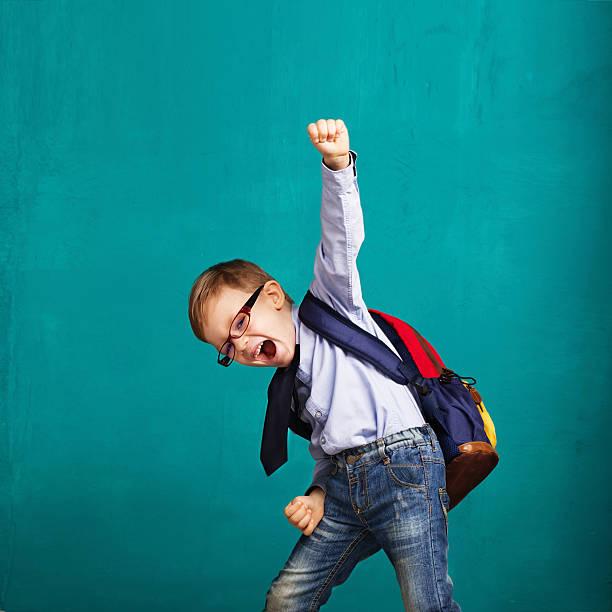niño sonriente con una mochila grande saltando y divirtiéndose - escuela primaria fotografías e imágenes de stock