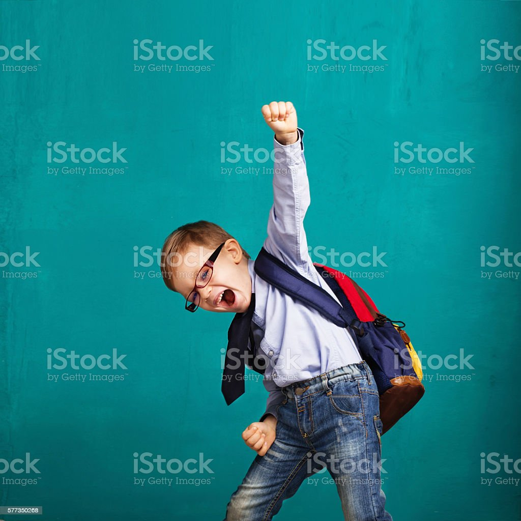 smiling little boy with big backpack jumping and having fun stock photo