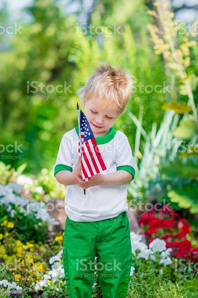 Smiling little boy with blond hair holding american flag stock photo