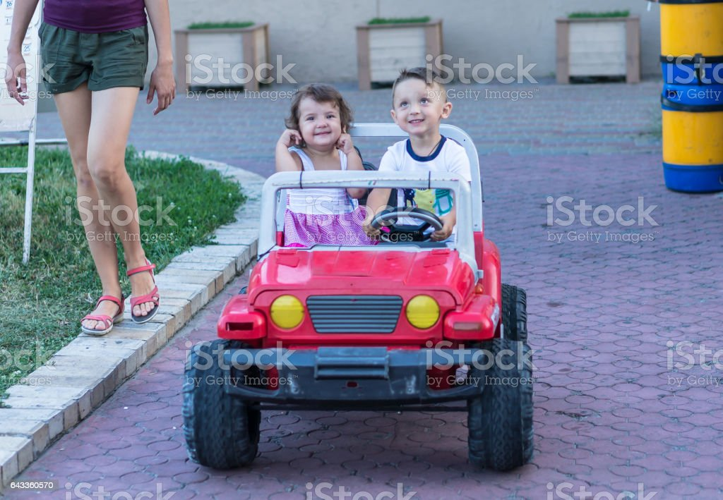 Smiling little brother and sister driving by toy car. Portrait of happy little kids on the street. Funny cute children making vacations and enjoying summer. Healthy lifestyle. Positive human emotions. stock photo