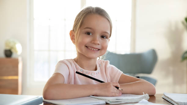 Smiling little child girl enjoying doing lessons at home. Head shot close up portrait of happy small pupil learning at home. Smiling little child girl enjoying doing lessons in living room. Smart kid schoolgirl looking at camera, studying remotely online. young girls on webcam stock pictures, royalty-free photos & images