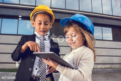 643843490istockphoto Smiling little engineers working together on digital tablet. 621732058