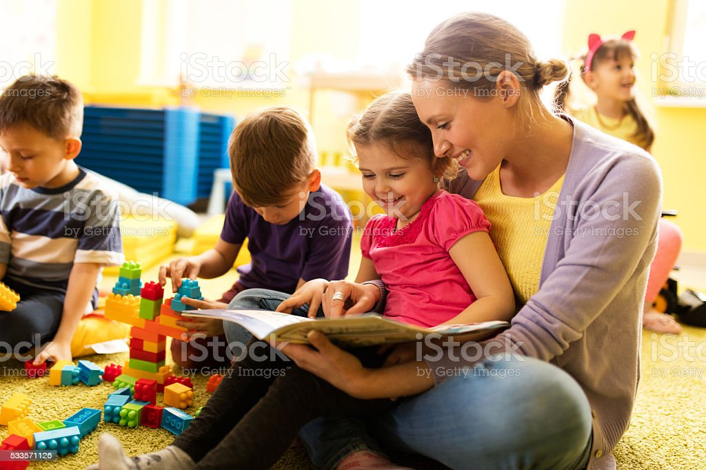 Smiling little girl and teacher reading a story at kindergarten. stock photo