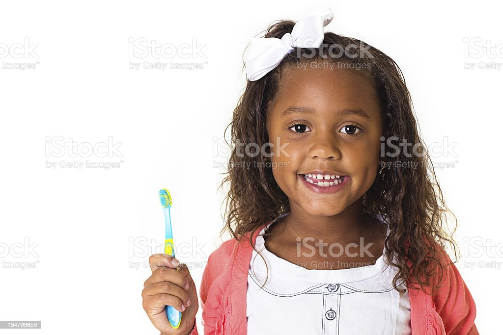 A smiling little girl brushing her teeth stock photo