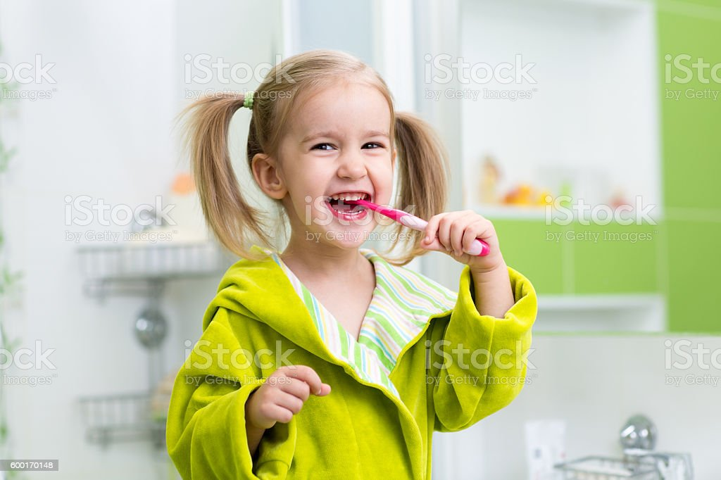 Smiling little girl brushing teeth in bathroom stock photo