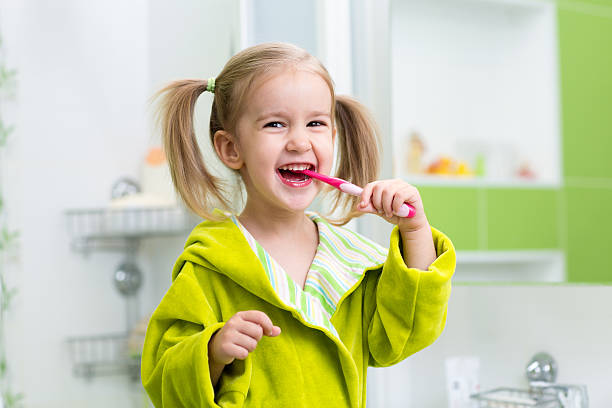 Smiling little girl brushing teeth in bathroom stock photo