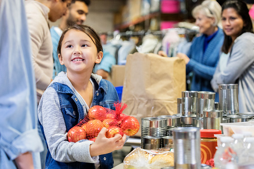 Happy little girl holds a bag of apples while volunteering with her family in a community food bank.