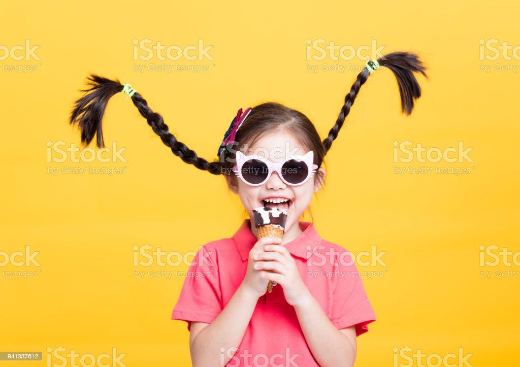 smiling little girl eating ice cream stock photo