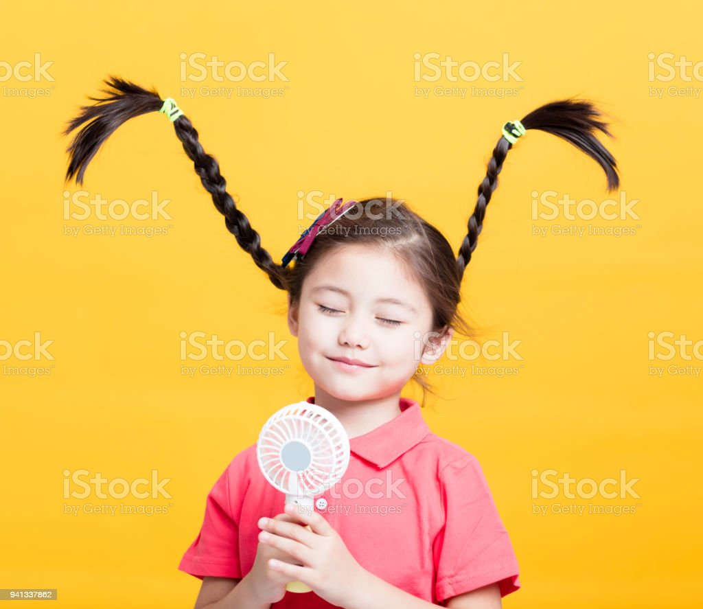 smiling little girl enjoying cool wind from electric fan royalty-free stock photo