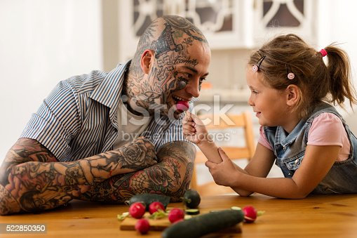 Tattooed smiling father being fed with a radish by his daughter in the kitchen.