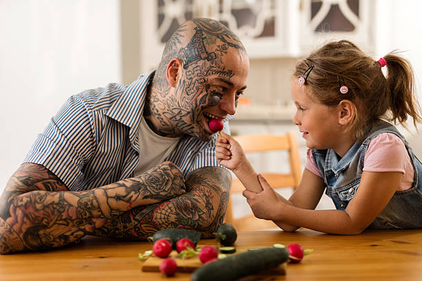 Smiling little girl feeding her father with a radish. stock photo