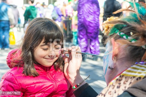 Smiling little girl getting her face painted by the face painter artist.