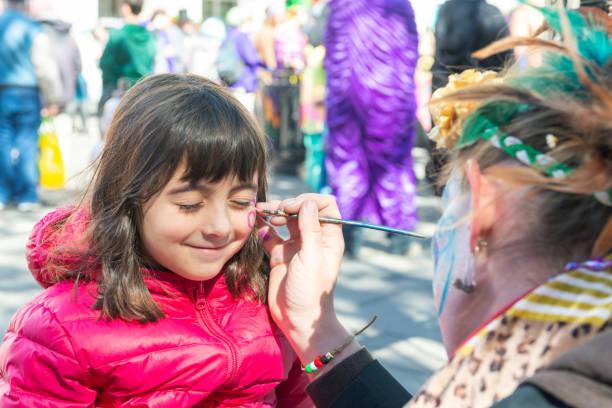glimlachend klein meisje krijgt haar gezicht geschilderd door het gezicht schilder kunstenaar - traditioneel festival stockfoto's en -beelden