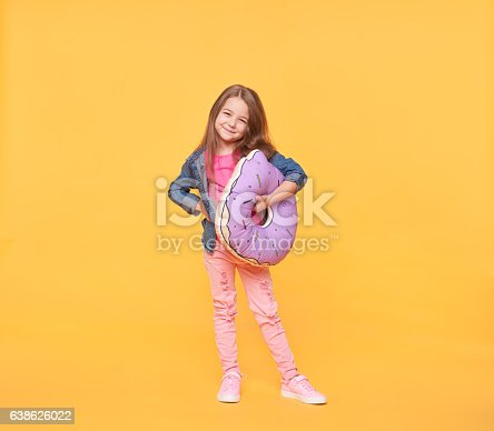 istock Smiling little girl holding a giant donut pillow 638626022