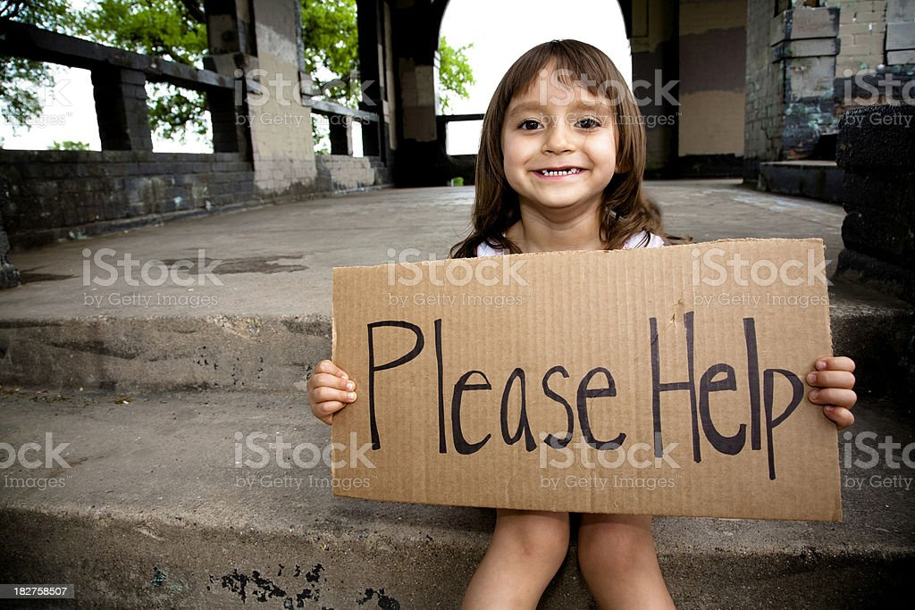 Smiling Little Girl Holding a Please Help Sign stock photo