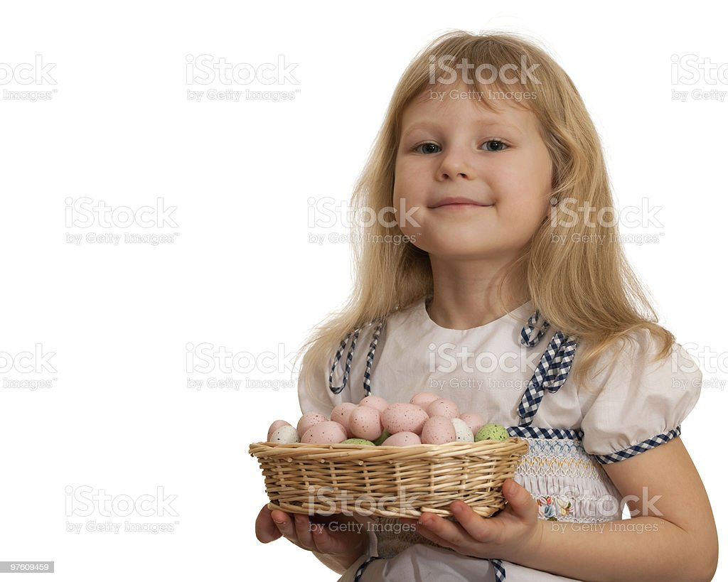 Smiling little girl holding Easter basket with eggs royaltyfri bildbanksbilder