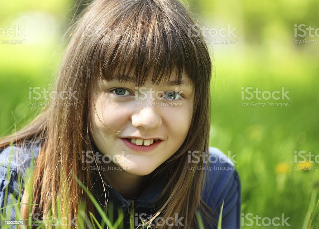 Smiling little girl in grass. stock photo