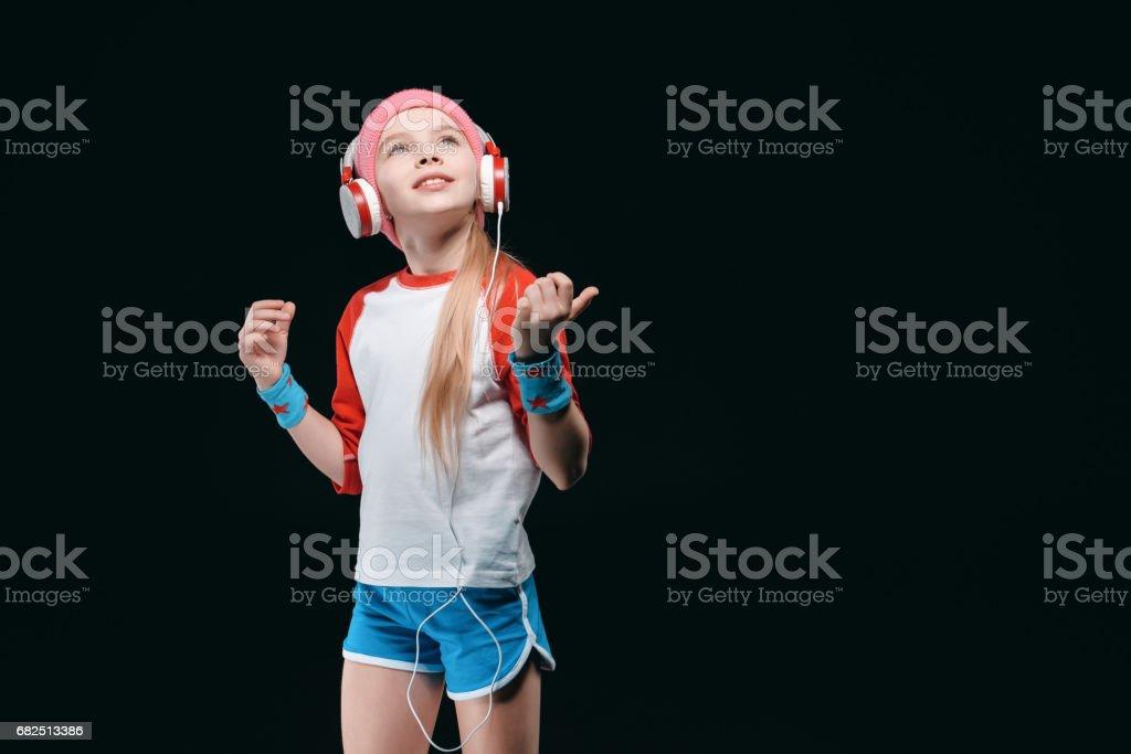 Kulaklıklar giyen ve izole üzerinde siyah, faaliyetleri çocuk kavramı için poz spor giyim gülümseyen küçük kız royalty-free stock photo