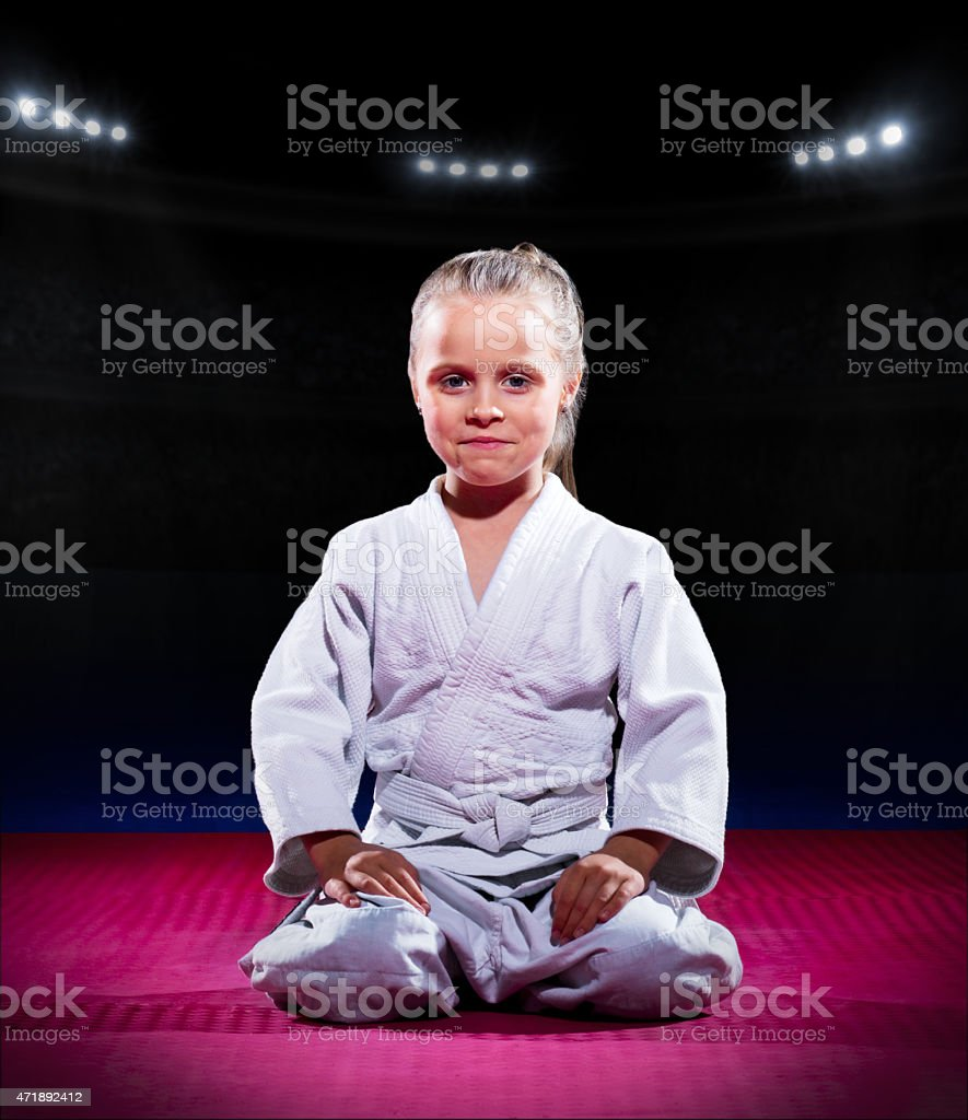 Smiling little girl in white aikido uniform waiting on mat stock photo