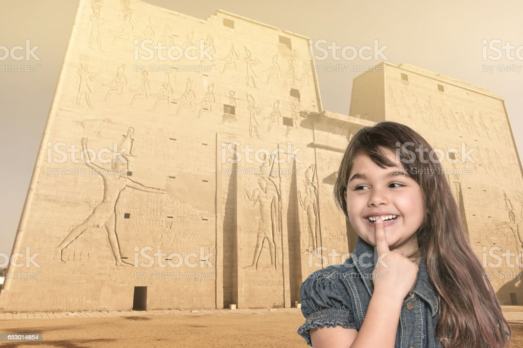 Smiling little girl is standing in front of Edfu temple in Egypt stock photo