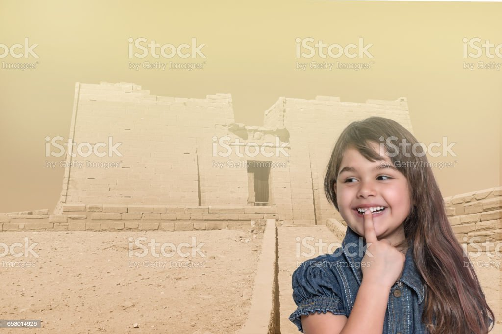 Smiling little girl is standing in front of the Temple of Kalabsha in Egypt stock photo