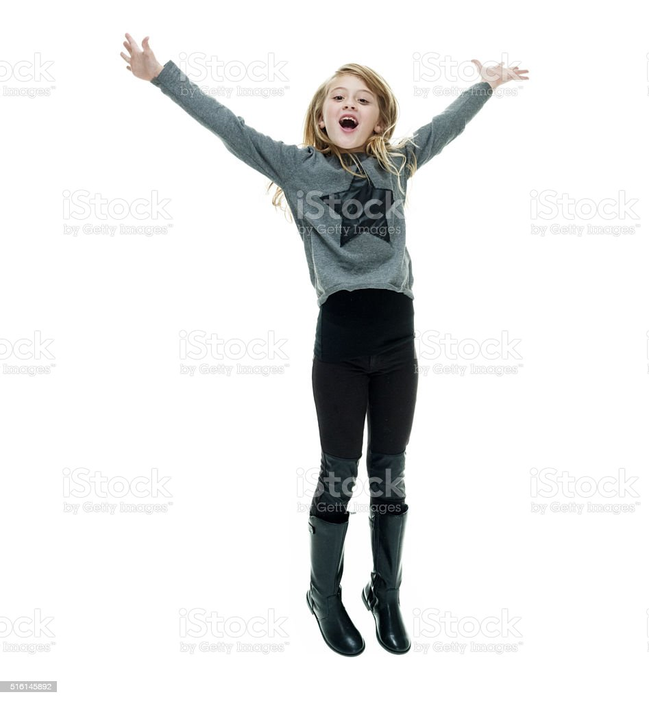 Smiling little girl jumping with arms outstretched stock photo