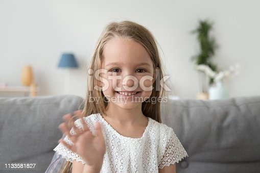 Smiling little girl looking at camera, waving hand, greeting, making video call to relatives, recording vlog for channel, head shot portrait of cute child, sitting on cozy sofa at home