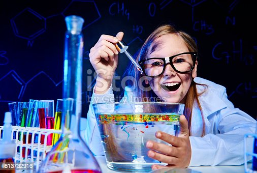 istock Smiling little girl making a experiment 813732916