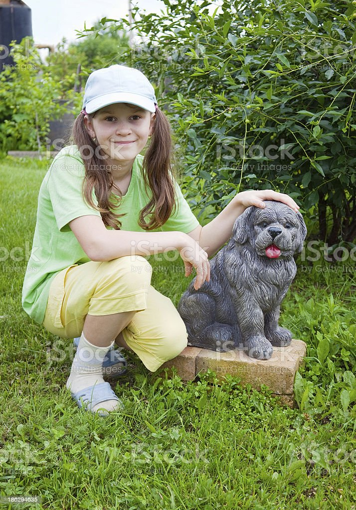 Smiling little girl near to concrete dog royalty-free stock photo