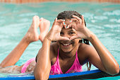 Eleven years old little girl looking at the camera smiling in the swimming pool gesturing a heart with her hands