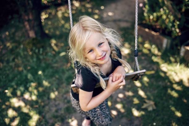 küçük kız bir salıncak yalnız oynamaya gülümseyen - kuzey ülkeleri stok fotoğraflar ve resimler