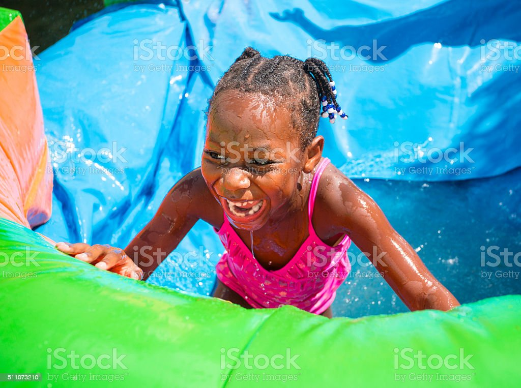 Smiling little girl playing on an inflatable water slide stock photo