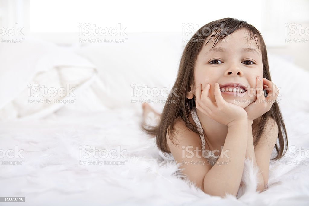 Smiling little girl playing with feathers in bed royalty-free stock photo