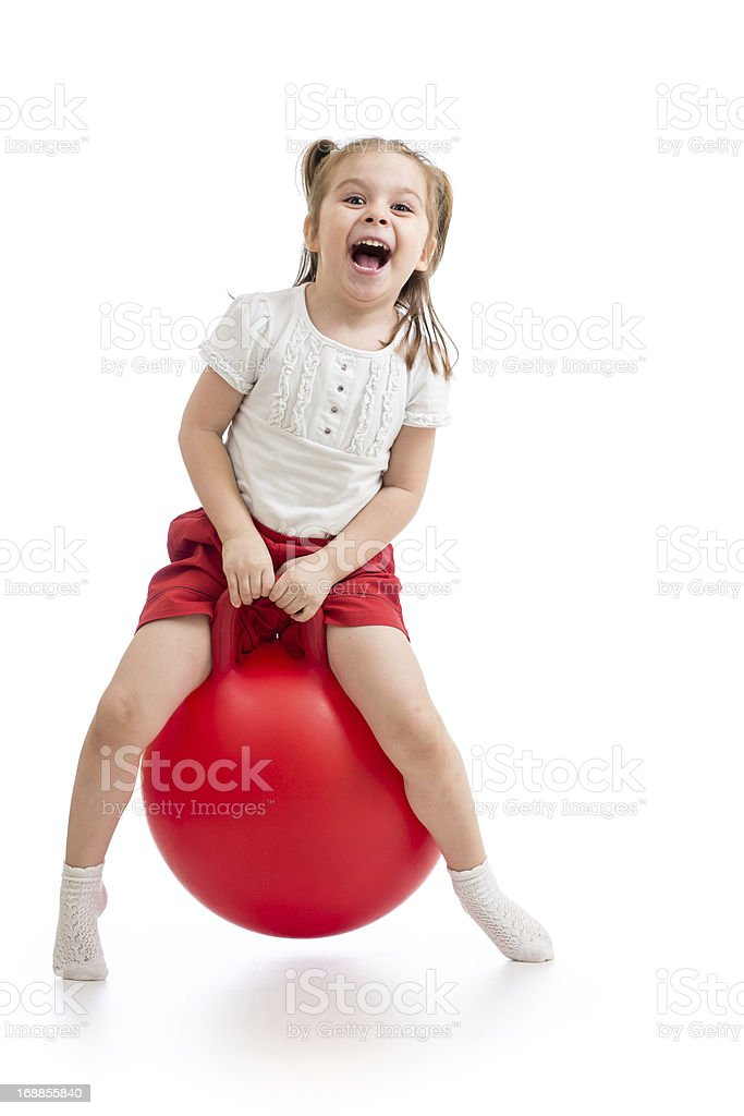 Smiling little girl playing with giant red bouncy ball stock photo