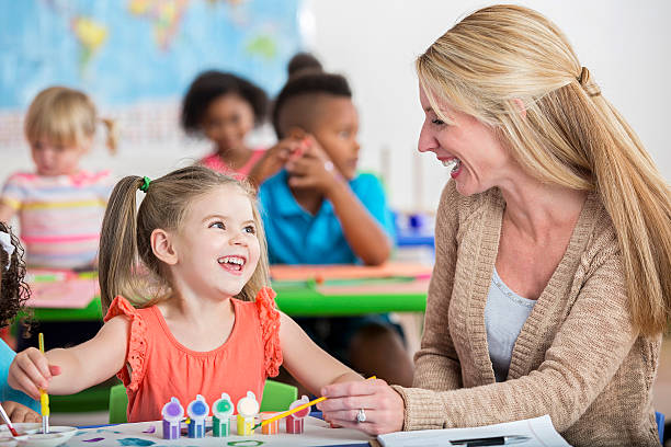 smiling little girl playing with paints at daycare with teacher - pigtails stock photos and pictures
