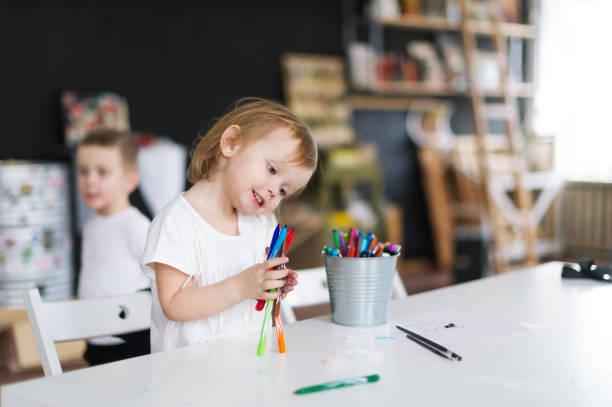 lächelnde mädchen spielen mit bleistiften auf dem tisch im kindergarten - kindergarten workshop stock-fotos und bilder