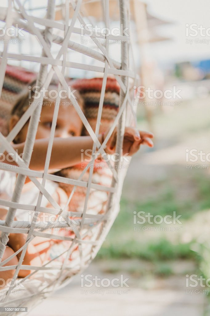 Smiling Little girl sitting in a hanging chair stock photo