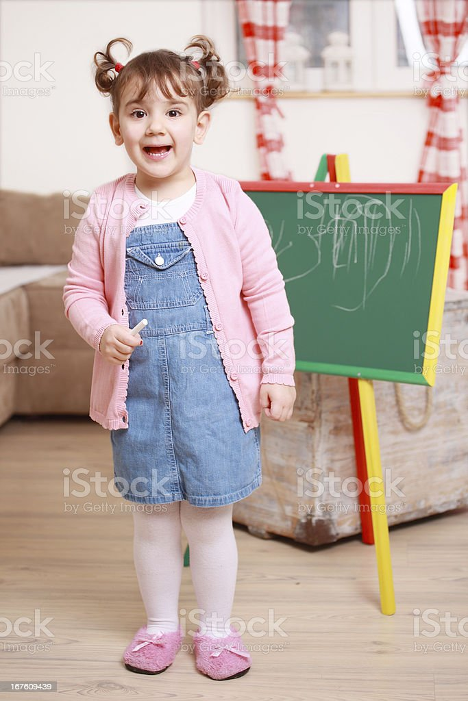 Smiling little girl standing near blackboard and holding a chalk royalty-free stock photo