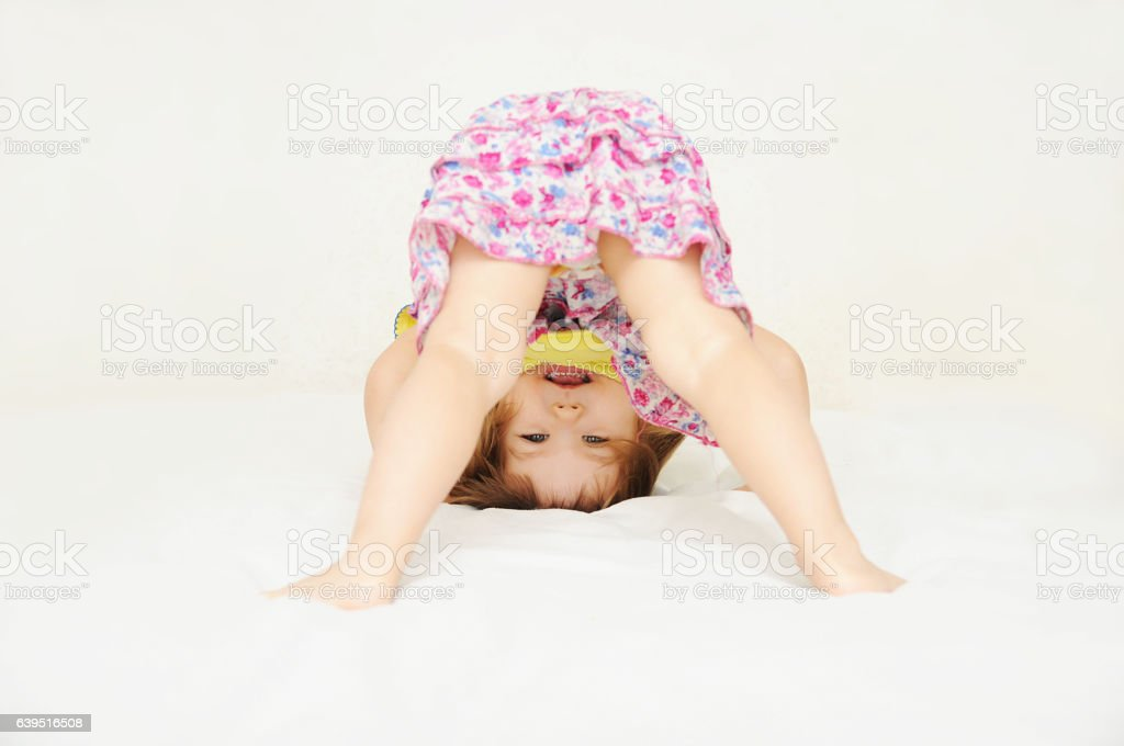 Smiling little girl standing on head upside down stok fotoğrafı