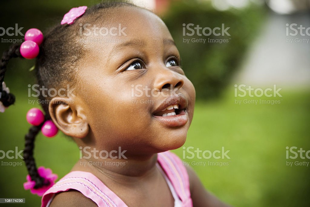 Smiling Little Girl Standing Outside and Looking Up royalty-free stock photo