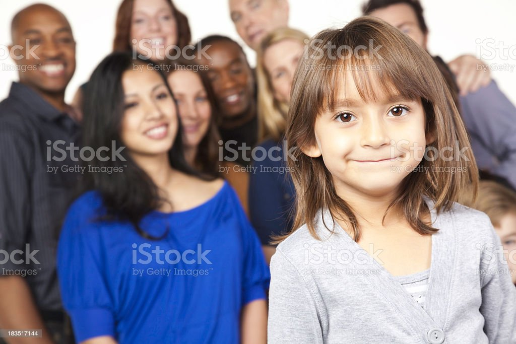 Smiling little girl stands in front of adult group royalty-free stock photo