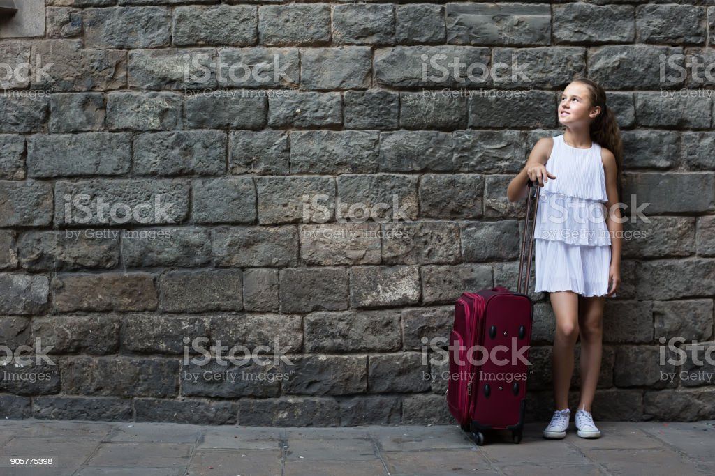 smiling little girl traveler with suitcase leaning against stone wall stock photo