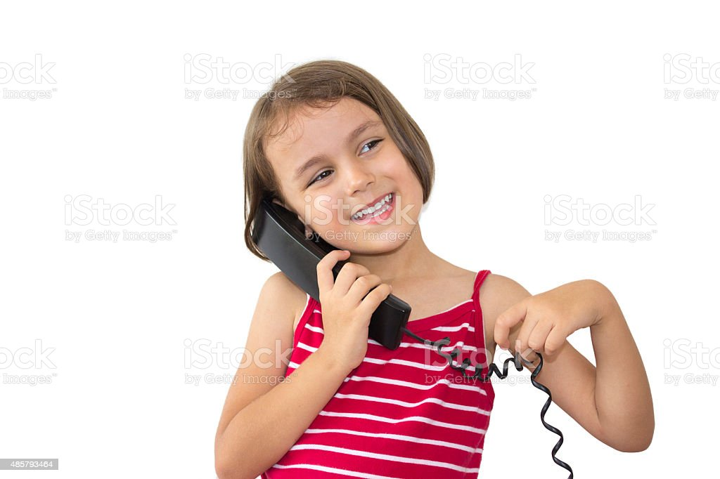 Smiling little girl using landline phone on white background stock photo