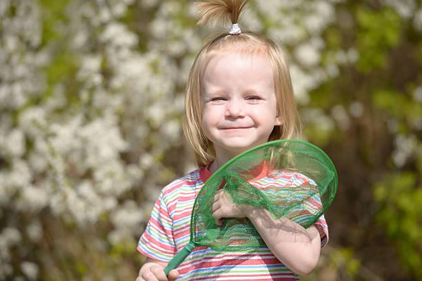 Cтоковое фото Улыбается Маленькая девочка с Сачок для бабочек