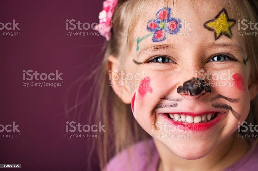Smiling little girl with a painted face stock photo