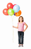 Full length portrait of a smiling girl with bunch of balloons. Vertical shot. Isolated on white.