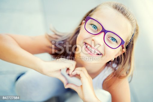istock Smiling little girl with dental braces and glasses showing heart with hands 842727584